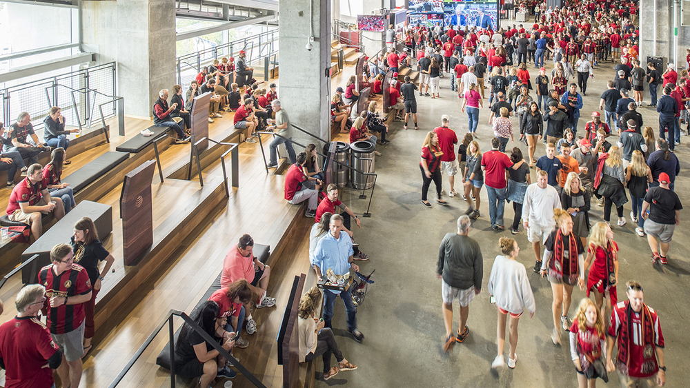 A crowd of people at The Perch, a space in Atlanta's Mercedes-Benz stadium where visitors can watch games and enjoy refreshments.